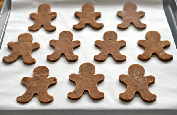 Raw gingerbread men on baking sheet Gingerbread men on baking sheet, uncooked cookie cutter stock pictures, royalty-free photos & images
