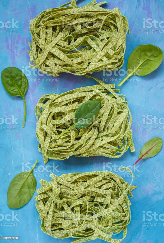 Raw green spinach pasta on a blue background, top view. stock photo