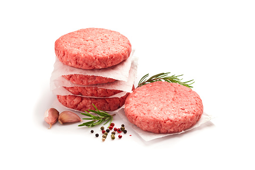 Two raw hamburger patties isolated white background. Predominant colors are red and white. Some cooking and seasoning ingredients like rosemary, garlic, peppercorns and oregano are around the burgers. DSRL studio photo taken with Canon EOS 5D Mk II and Canon EF 100mm f/2.8L Macro IS USM