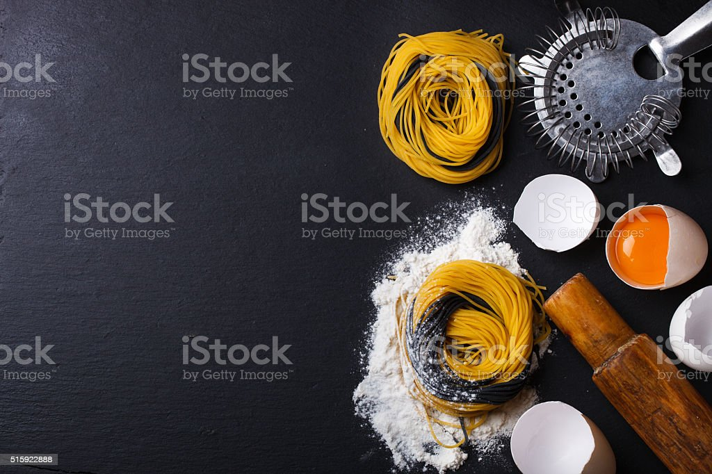 Raw homemade pasta and ingredients on a black background stock photo