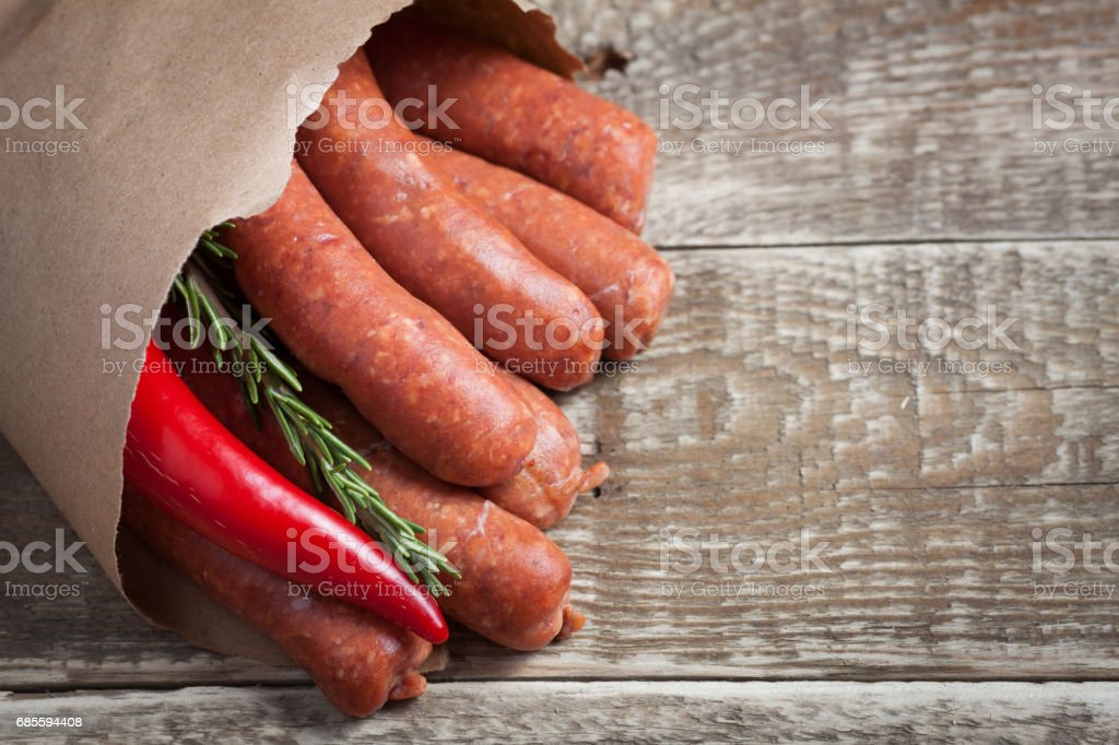 Raw homemade sausages of lamb with rosemary and chili pepper in a paper envelope on a black wooden Board 免版稅 stock photo