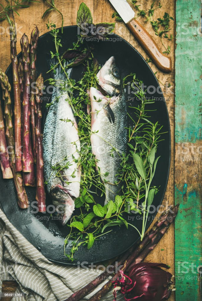 Raw incooked sea bass with herbs royalty-free stock photo