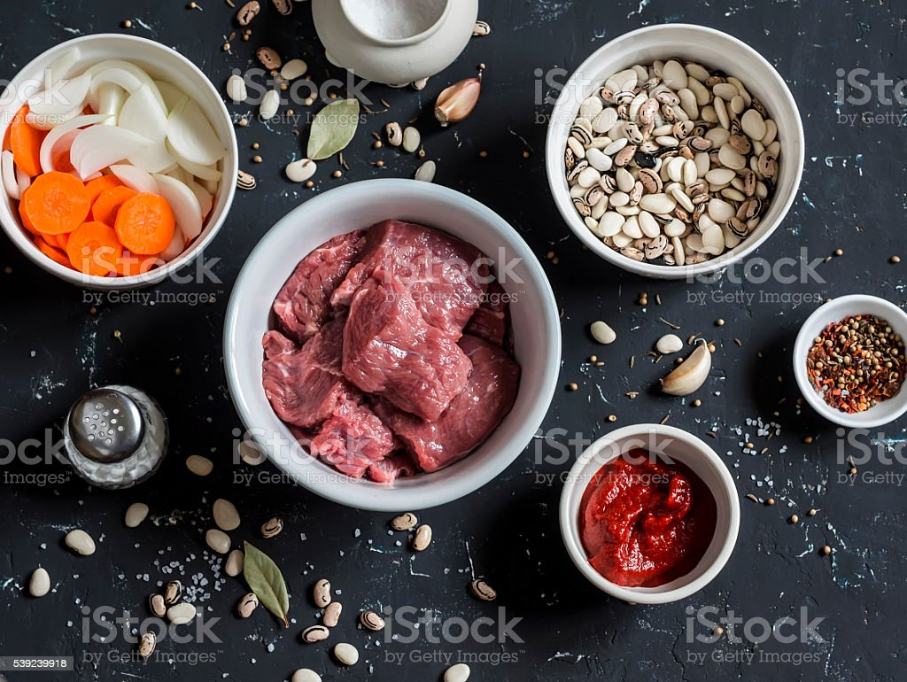 Raw ingredients - beef, beans, onions, carrots, spices, tomato sauce royalty-free stock photo