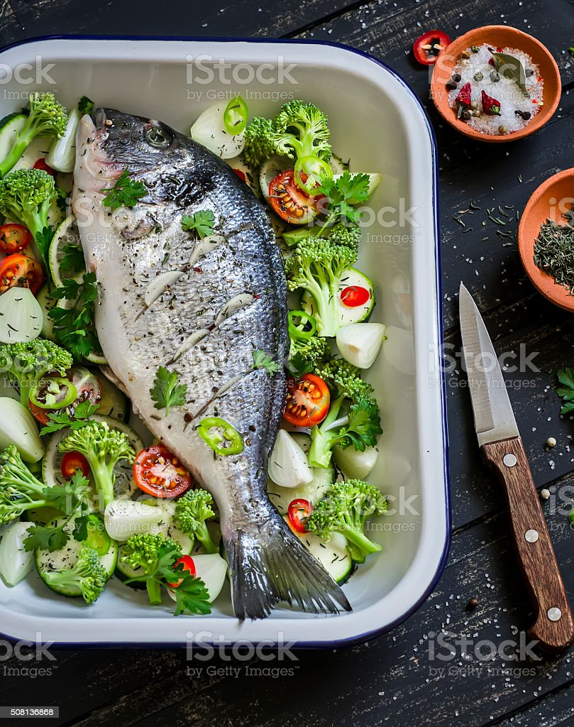 raw ingredients - dorado fish and vegetable, cooking baked fish stock photo