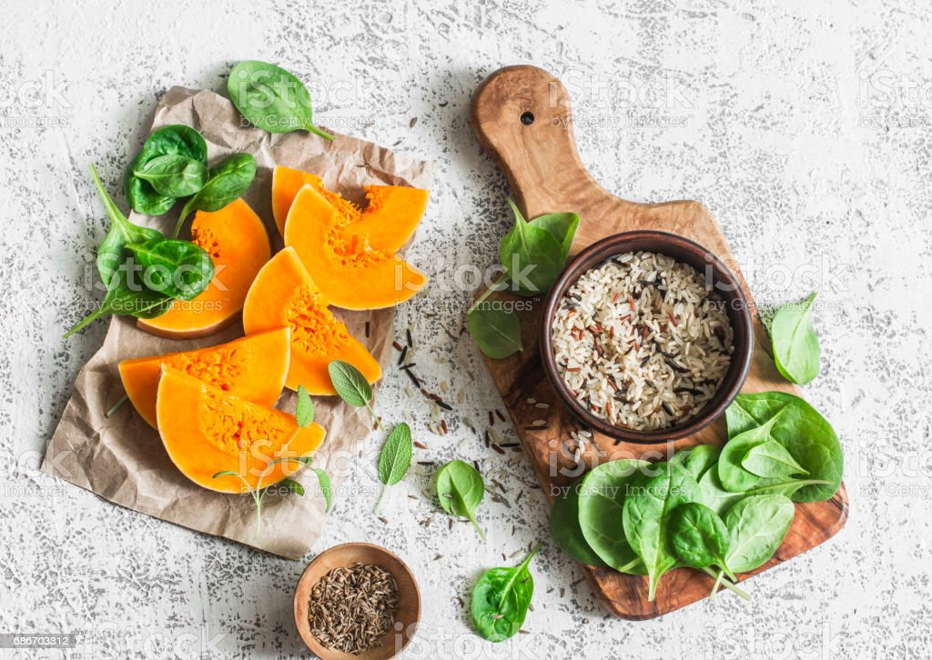 Raw ingredients for cooking vegetarian lunch - pumpkin, wild rice, spinach, spices on a light table, top view. Flat lay stock photo
