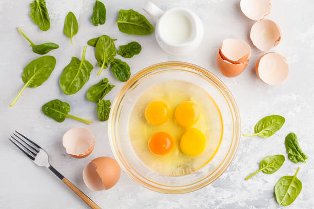 Raw ingredients for omelette with milk and spinach. Breakfast concept, top view, copy space. Raw ingredients for omelette with milk and spinach. Breakfast concept, top view animal egg stock pictures, royalty-free photos & images