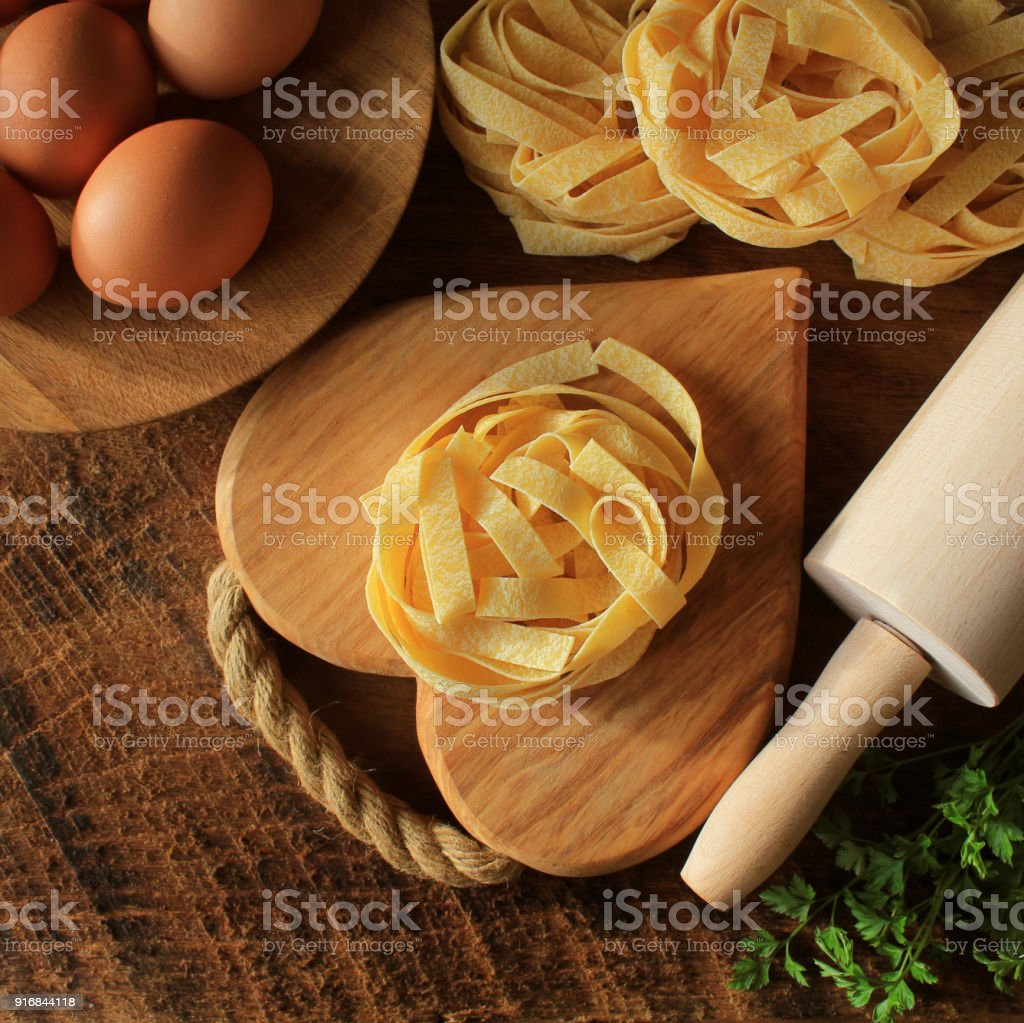 Raw italian pasta tagliatelle on wooden board and rolling pin on rustic background. Selective focus stock photo