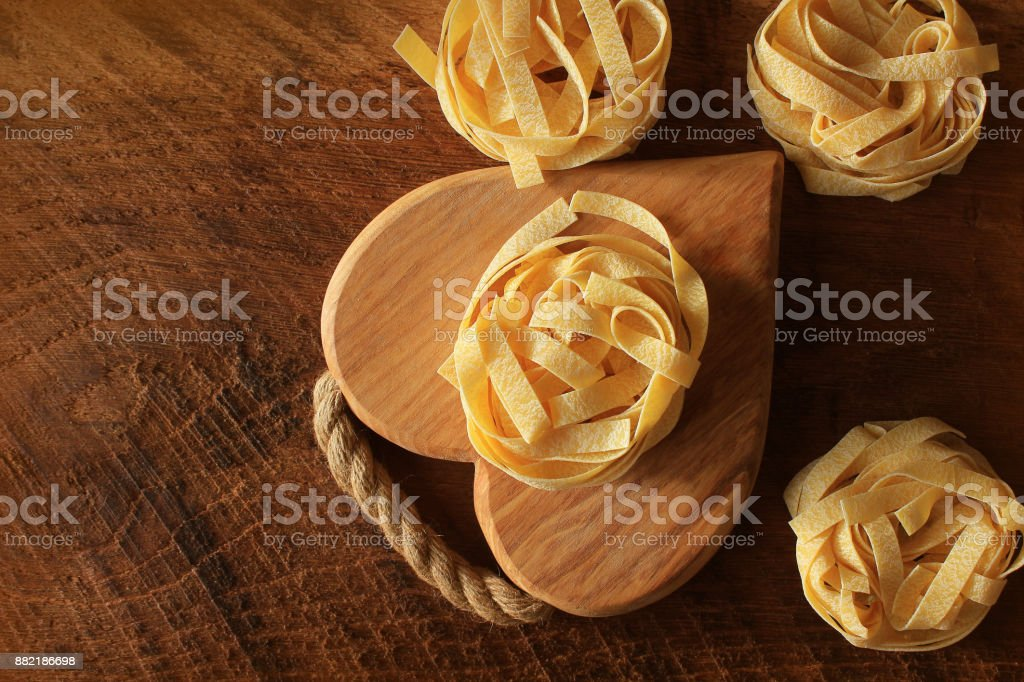 Raw italian pasta tagliatelle on wooden cutting board . Top view stock photo
