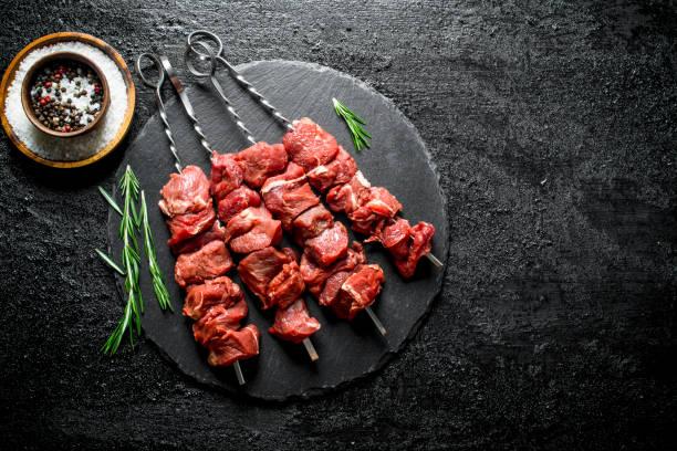rohkebab auf einem steinbrett mit rosmarin und gewürzen. - kebab marinade stock-fotos und bilder