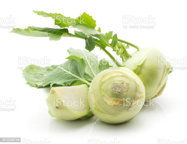 Kohlrabi (German turnip or turnip cabbage) two bulbs and one sliced quarter with fresh leaves isolated on white background