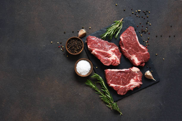 raw marbled beef steak on a stone board. spices, dishes. top view flat lay with copy space. - beef angus imagens e fotografias de stock