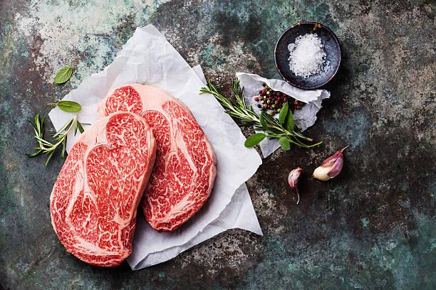 bravo marmoreado crus de carne bife ribeye e temperos - beef angus imagens e fotografias de stock