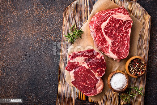 Raw marbled ribeye steak. Fresh meat and spices. Top view
