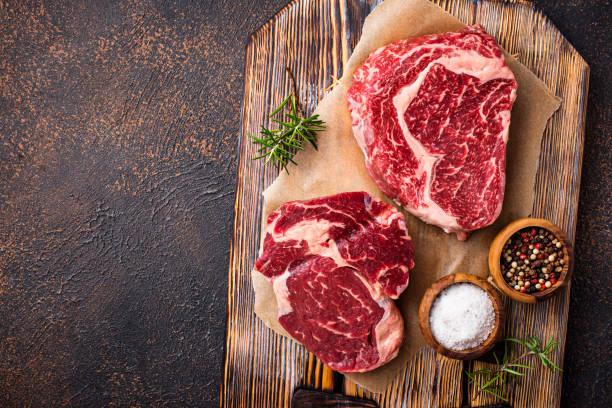 rauwe gemarmerde ribeye steak en specerijen - ribeye biefstuk stockfoto's en -beelden