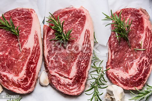 istock Raw marbled steaks on white paper , top view, close up 615405822