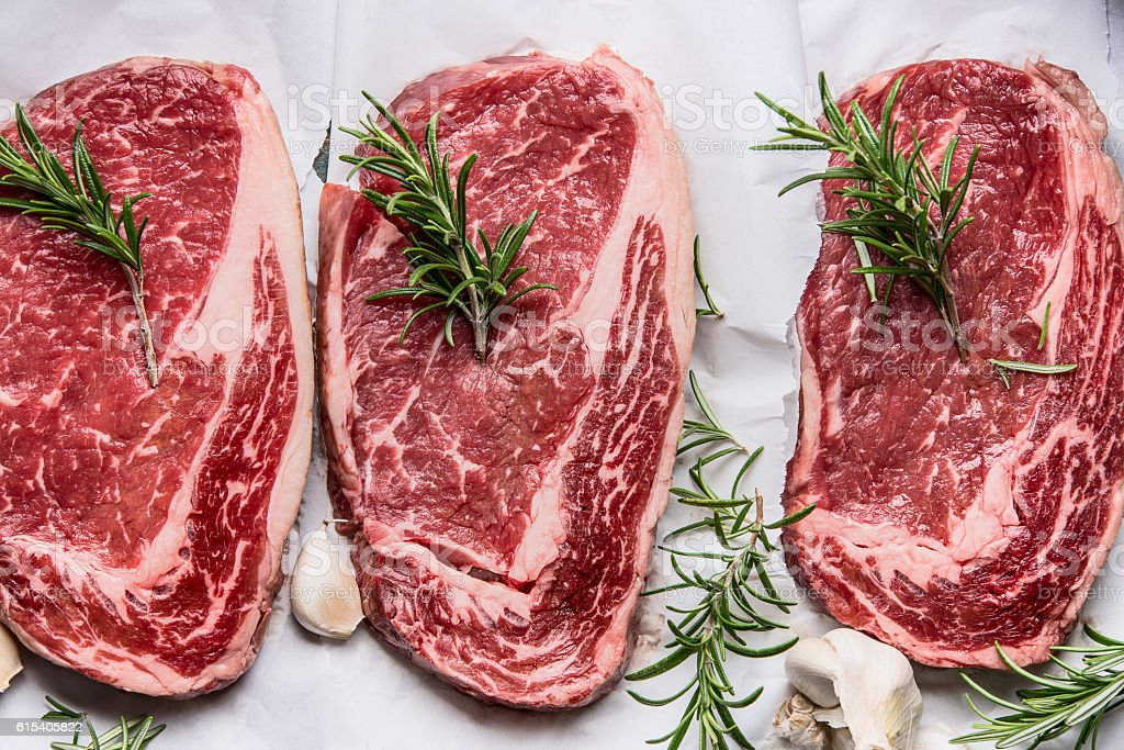 Raw marbled steaks on white paper , top view, close up stock photo