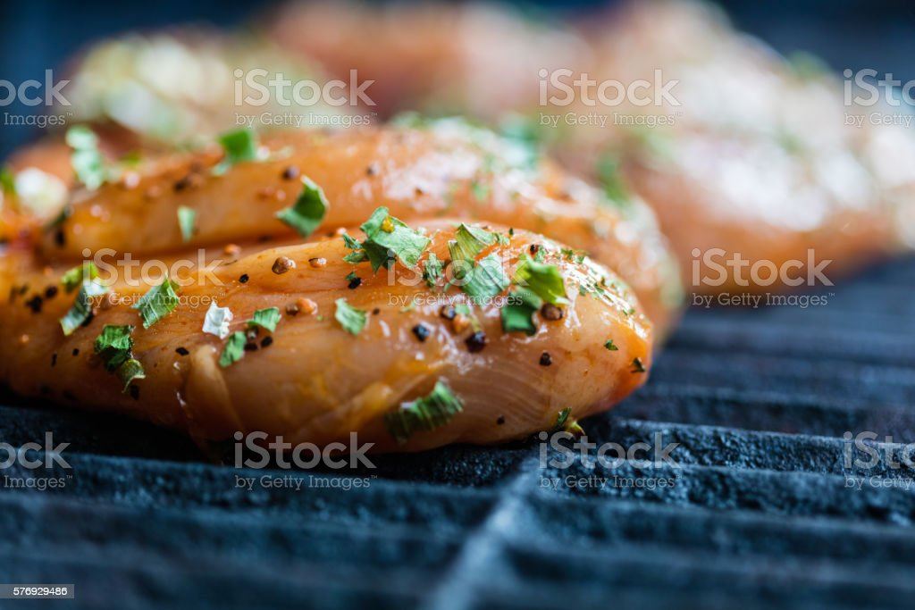 Raw marinated chicken breasts cooking on the BBQ stock photo