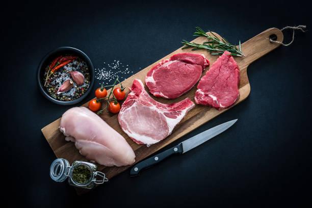 rohes fleischsortiment - rinder-, hühner- und schweinekoteletts von oben auf dunklem hintergrund - fleisch stock-fotos und bilder