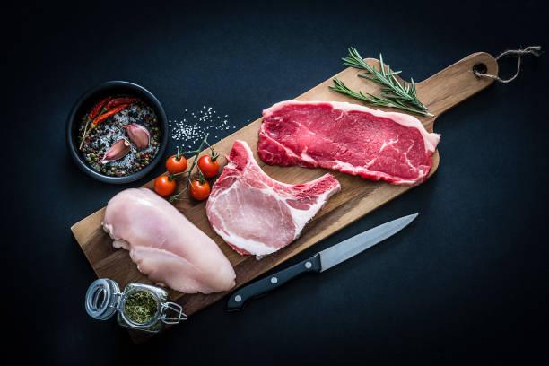 Rohes Fleischsortiment - Rinder-, Hühner- und Schweinekoteletts von oben auf dunklem Hintergrund – Foto