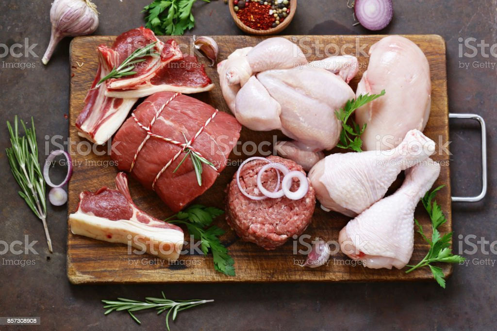 raw meat assortment - beef, lamb, chicken on a wooden board stock photo