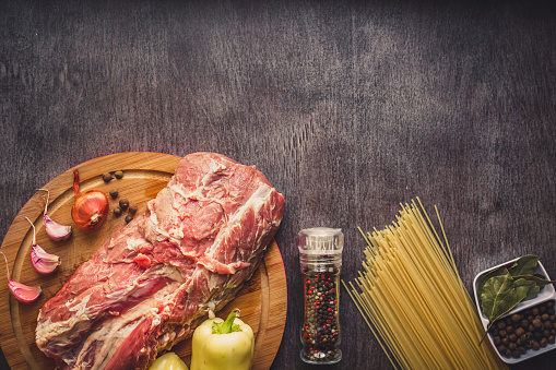 Raw meat beef slices on a wooden cutting board with spaghetti, garlic, spices, peppercorns, salt and dill for cooking pasta. Top view