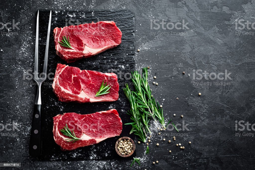 Raw meat, beef steak on black background, top view royalty-free stock photo