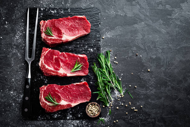 raw meat, beef steak on black background, top view - meat stock photos and pictures