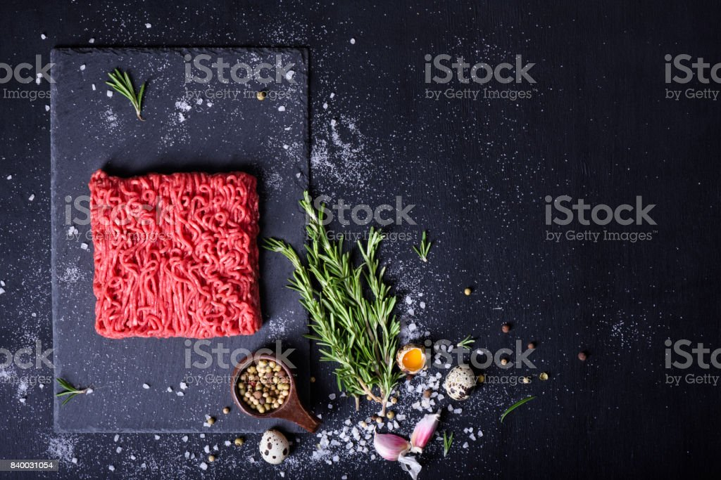 Raw meat, beef steak on black background, top view, stock photo