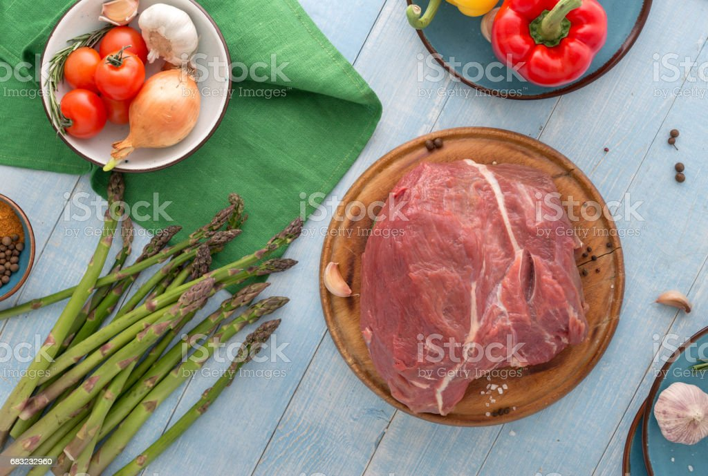 Raw meat. Fresh beef tenderloin on cutting board on blue wooden table with different vegetables royalty-free stock photo