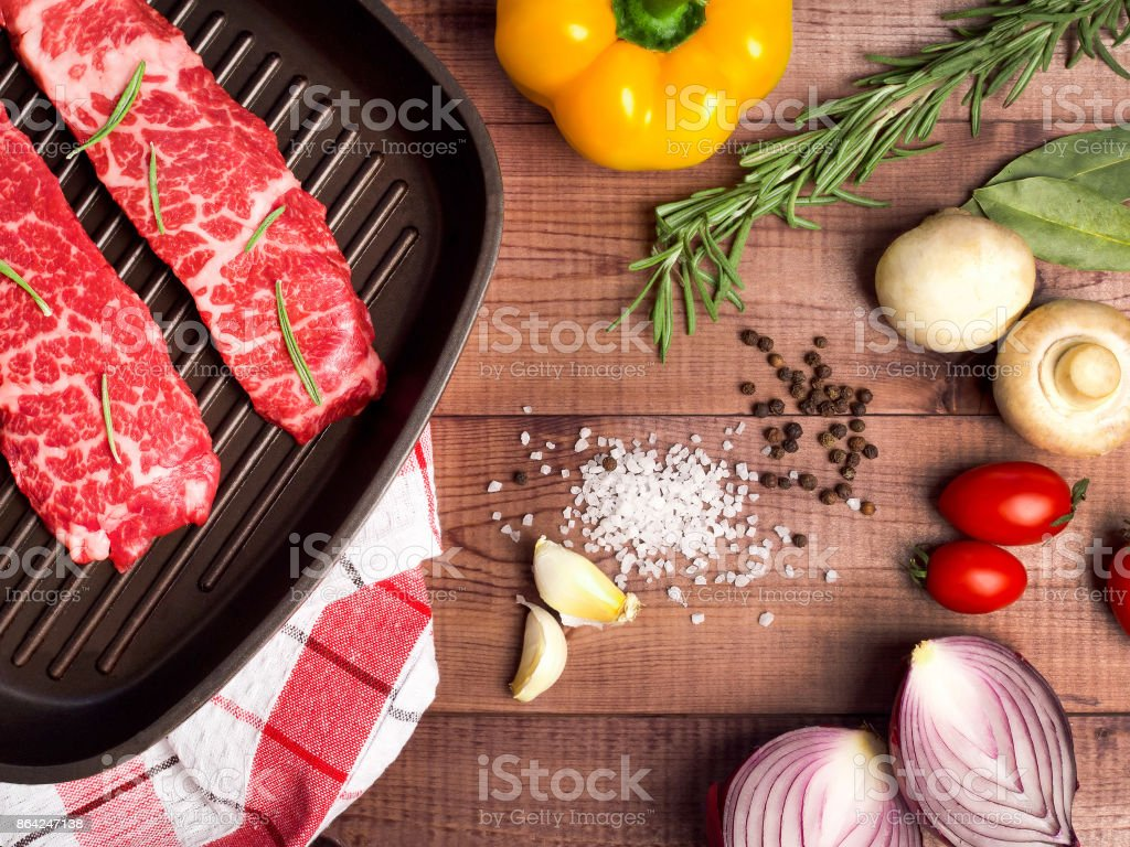 Raw meat in a frying pan on brown boards. Nearby spices, condiments and vegetables. royalty-free stock photo