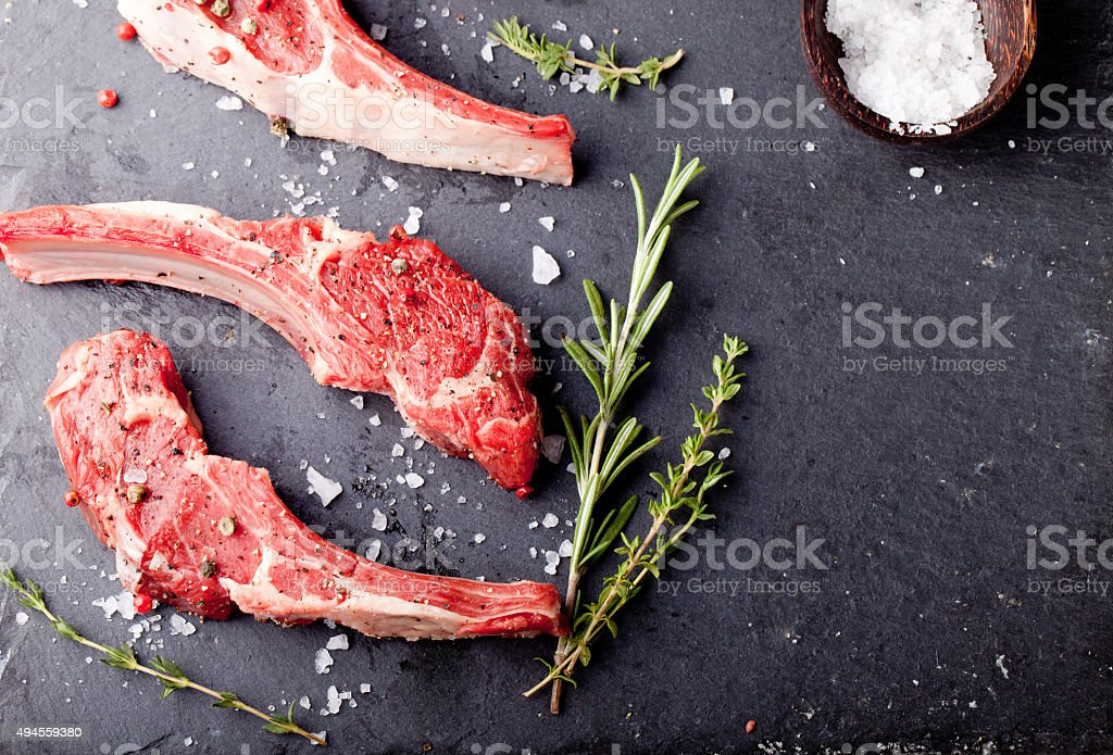 Raw meat, mutton, lamb rack with fresh herbs. stock photo