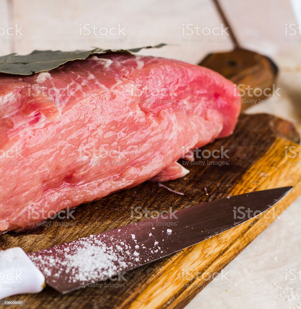 raw meat on a cutting board with spices, knife stock photo