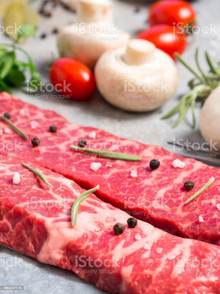 Raw meat on a sheet of tin. Nearby spices, condiments and vegetables. royalty-free stock photo