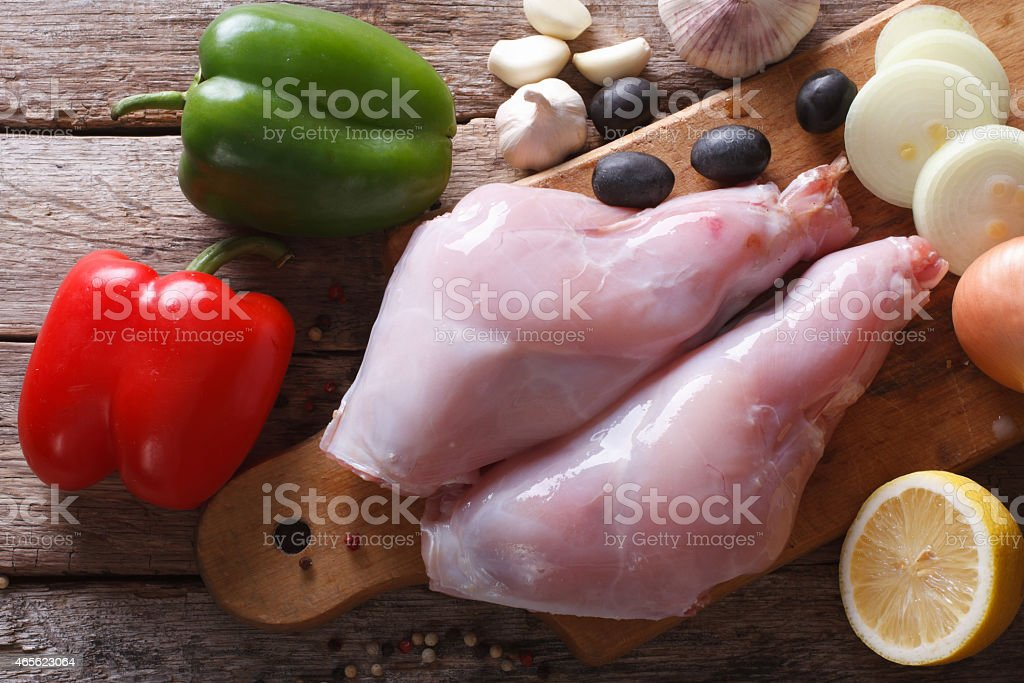 Raw meat rabbit legs and vegetables close-up top view stock photo