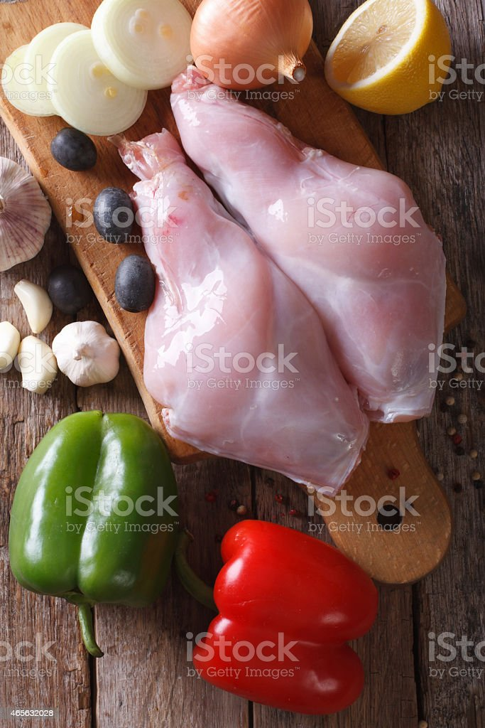 Raw meat rabbit legs and vegetables closeup top view vertical stock photo