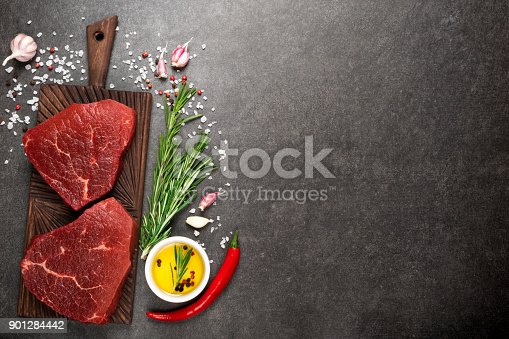 808351094istockphoto Raw meat. Raw beef steak on cutting board with rosemary and spices 901284442
