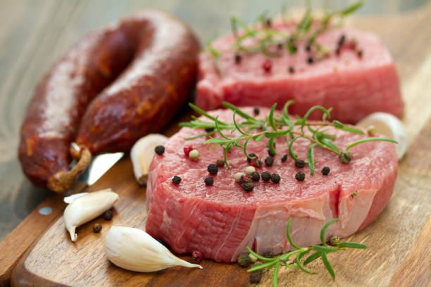 carne con chorizo ahumado, pimienta y ajo en tablero de madera sobre fondo marrón - foto de stock