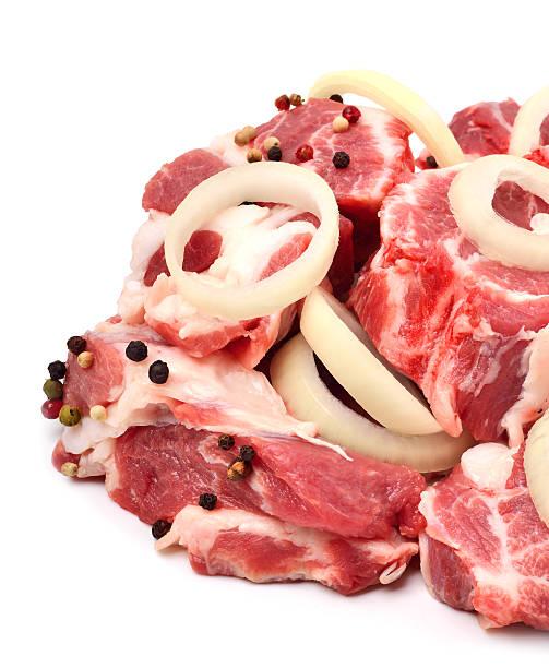 raw die stücke mit geschnittene zwiebeln und schwarzem pfeffer - schweinegulasch stock-fotos und bilder