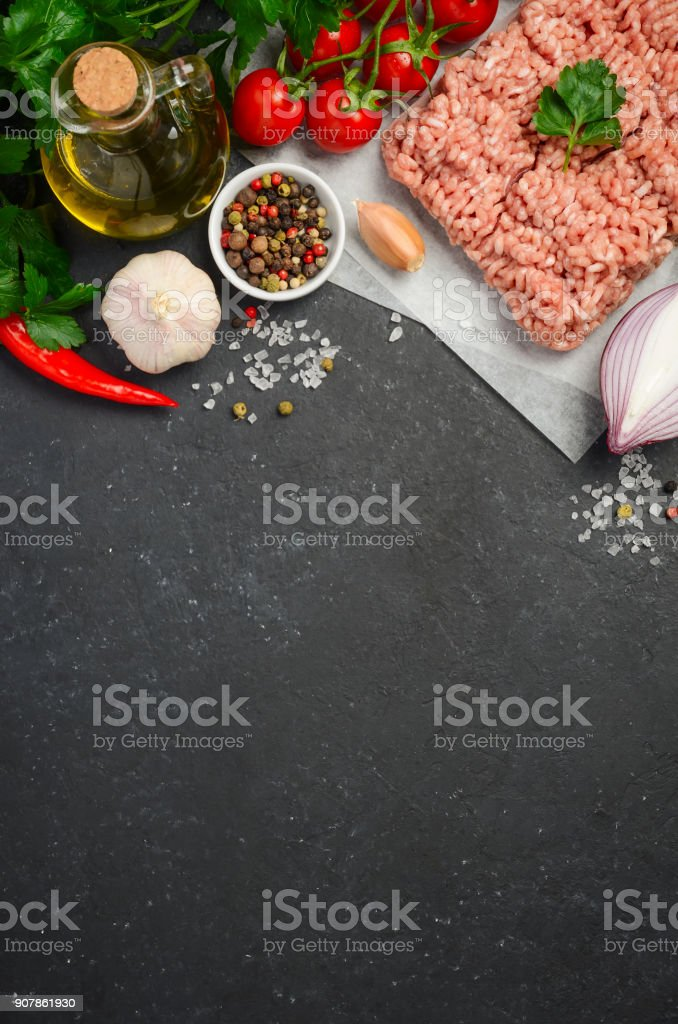 Raw minced meat on paper with fresh vegetables and spices on black background. stock photo