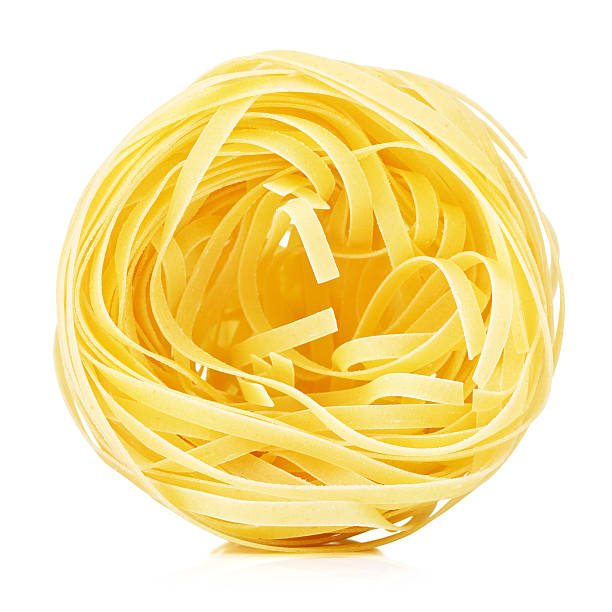 Raw Nest Pasta raw pasta tagliatelle nest, isolated on white tagliatelle stock pictures, royalty-free photos & images