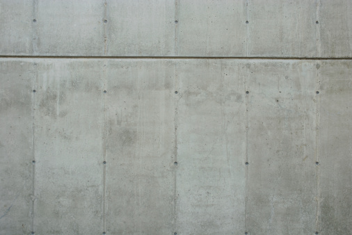 Fresh new concrete wall background with construction formwork lines and tie hole plugs