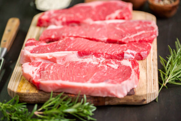rauw new york strip steaks op een houten snijplank. - strip steak stockfoto's en -beelden