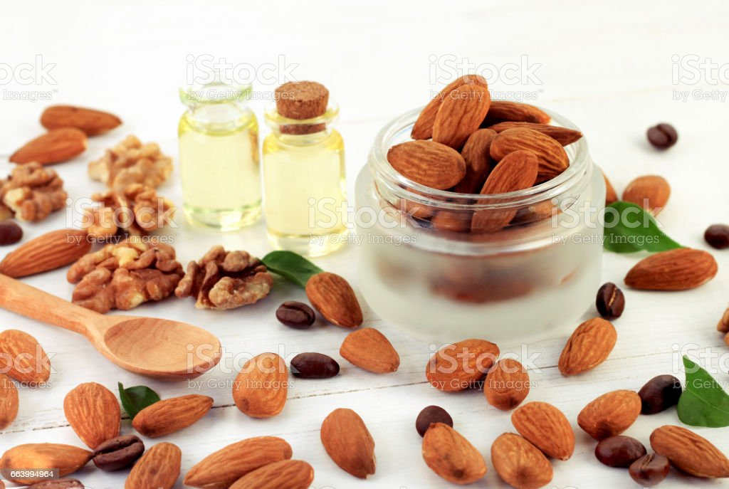 Raw Nuts in cosmetic jar, almond and walnut, oil bottles in background. stock photo