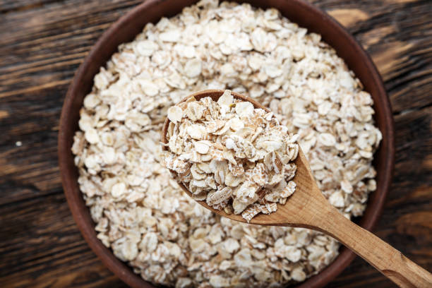 raw oatmeal in a bowl with a wooden spoon on a napkin of burlap stock photo