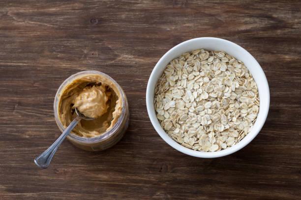 Rohes Haferflocken in einer weißen Schüssel mit Erdnussbutter, Zutaten für ein leckeres gesundes Frühstück auf Holzhintergrund – Foto