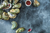 Raw ocean oysters with glass of white wine and limes on dark table. Flat lay. Top view. Food background
