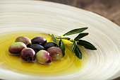 Raw olive and olive oil in wood plate.