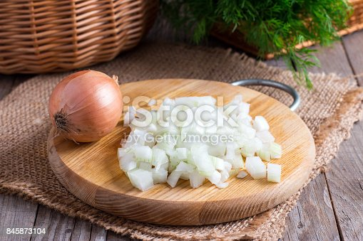 Raw onion, chopped very small cubes on a wooden board