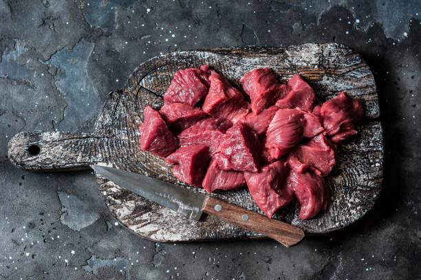 Rohes Bio-Rinderfilet-Fleischstück auf rustikalem Holzbrett auf dunklem Hintergrund, oben. Lebensmittelzutaten – Foto