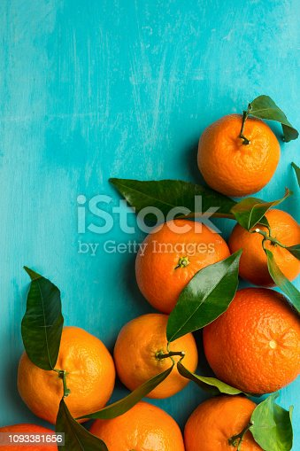 istock Raw organic juicy tangerines on branch with green leaves on mint blue turquoise wooden table. Vitamins healthy lifestyle harvest concept. Vibrant colors. Beautiful food poster 1093381656